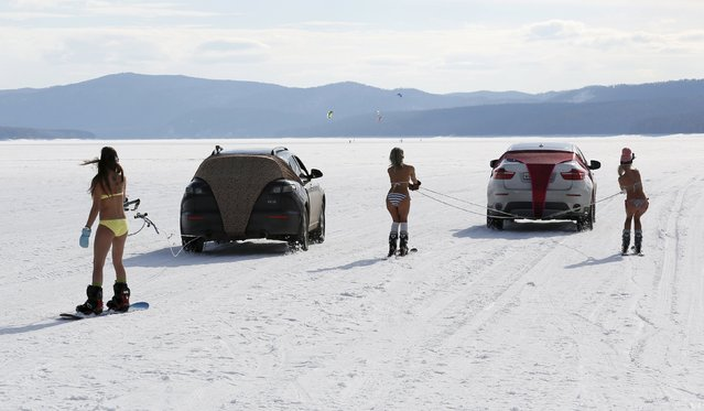 Bikini-clad women ski and snowboard as they are led by cars during a performance on the frozen Yenisei River outside Krasnoyarsk, Siberia, Russia, March 20, 2016. (Photo by Ilya Naymushin/Reuters)