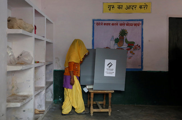 A woman looks at the Electronic Voting Machine (EVM) before casting her vote inside a booth at a polling station during the state assembly election in Hapur, in the central state of Uttar Pradesh, India, February 11, 2017. (Photo by Adnan Abidi/Reuters)