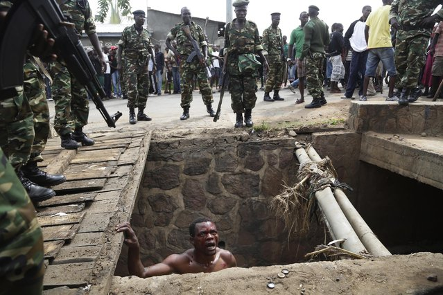 Jean Claude Niyonzima, a suspected member of the ruling party's Imbonerakure youth militia, pleads with soldiers to protect him from a mob of demonstrators after he emerged from hiding in a sewer in the Cibitoke district of Bujumbura, Burundi, Thursday May 7, 2015. (Photo by Jerome Delay/AP Photo)