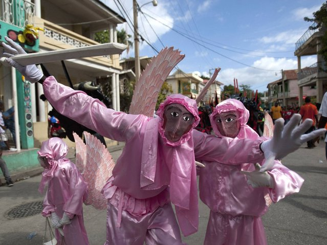 """Revelers dressed as Archangel St. Michael dance during Carnival celebrations in Jacmel, Haiti, Sunday, February 23, 2014. The pre-Lent celebrations later this week will be in the western port city of Gonaives, under the government's effort to """"decentralize"""" Carnival by holding festivities in different towns in the countryside each year. (Photo by Dieu Nalio Chery/AP Photo)"""
