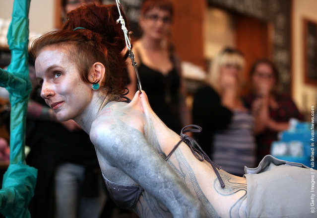 Alice Newstead inspects shark hooks that she had pierced into her skin during a demonstration against the shark fin trade