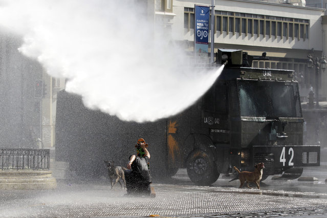 A protester confronts a jet of water shot from a police operated water cannon, during a student protest, in Santiago, Chile, Thursday, May 14, 2015. (Photo by Luis Hidalgo/AP Photo)