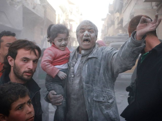A Syrian man holds a crying girl as he gestures following an air strike by government forces on the Sahour neighbourhood of the northern Syrian city of Aleppo on March 6, 2014. (Photo by Fadi Al-Halabi/AFP Photo/AMC)