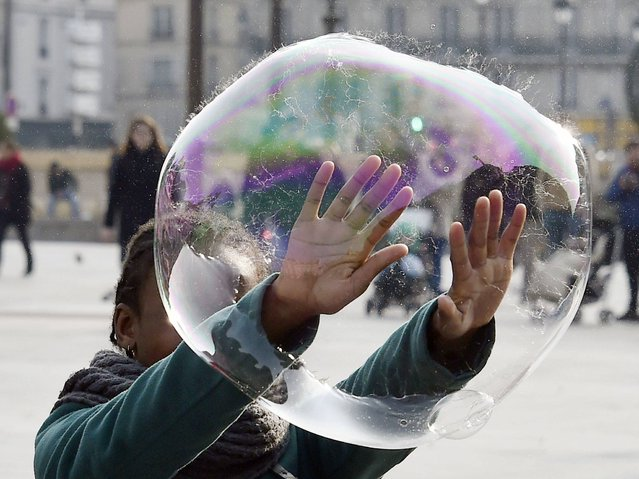 A child plays with a soap bubble on the city hall plaza on March 14, 2015 in Paris. (Photo by Dominique Faget/AFP Photo)