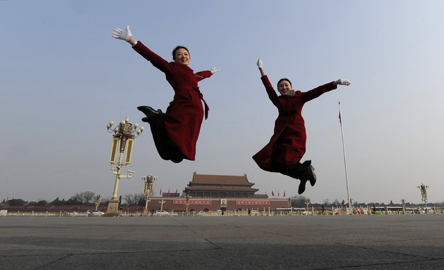 Hotel guides jump as they pose for photographs in front of the Tiananmen Gate and the giant portrait of Chinese late chairman Mao Zedong, near the Great Hall of the People during a plenary session of the National People's Congress (NPC) in Beijing March 9, 2014. (Photo by Reuters/Stringer)
