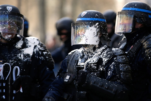 Riot police are covered in paint during clashes within a demonstration of high school students protesting against the government's planned labor reform on April 5  in eastern Paris. The Socialist government is desperate to push through reforms to France's controversial labour laws, billed as a last-gasp attempt to boost the flailing economy before next year's presidential election. (Photo by Kenzo Tribouillard/AFP Photo)
