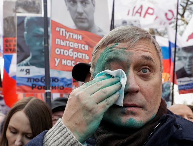 Mikhail Kasyanov, Russian opposition leader, wipes his face after green paint was thrown at him during a rally to mark anniversary of murder of Kremlin critic Boris Nemtsov in Moscow, Russia, February 26, 2017. (Photo by Tatyana Makeyeva/Reuters)