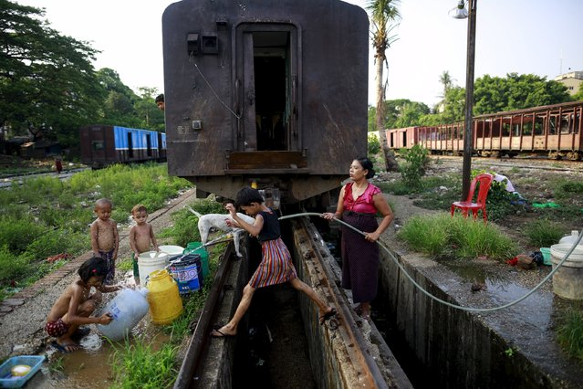 Children play as their mother collects water at a train station in Yangon May 11, 2015. (Photo by Soe Zeya Tun/Reuters)