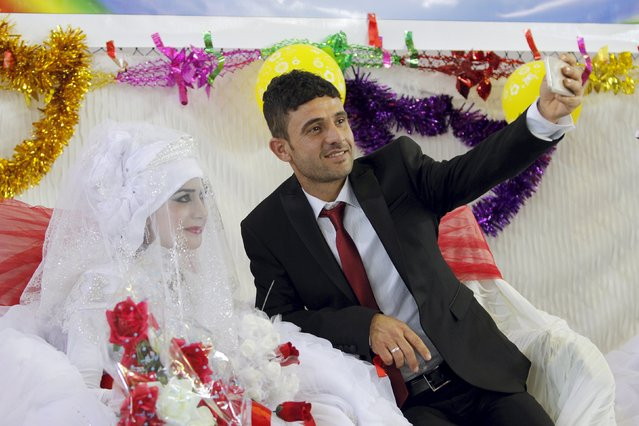 A groom takes a selfie with his bride during a mass wedding ceremony for Turkmen who are displaced and have fled the violence in the province of Nineveh, in Kirkuk, Iraq, April 7, 2016. (Photo by Ako Rasheed/Reuters)