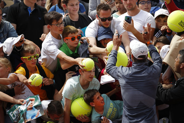Spain's Rafael Nadal and his security guard right, ask fans to calm down to prevent children from getting crushed after Nadal's second round match of the French Open tennis tournament against Germany's Yannick Maden at the Roland Garros stadium in Paris, Wednesday, May 29, 2019. (Photo by Christophe Ena/AP Photo)
