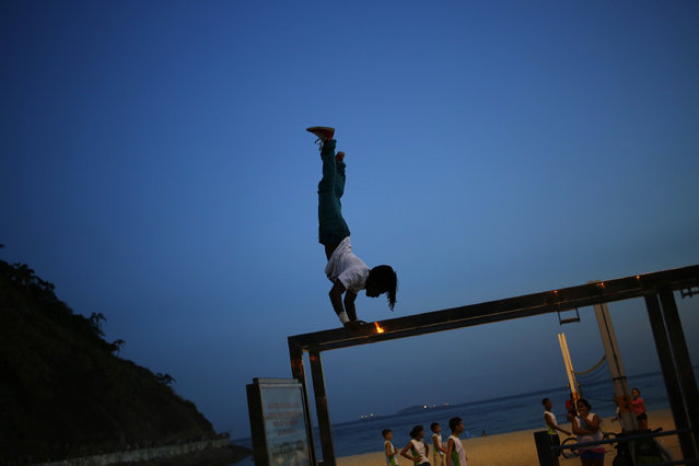 A man exercises in front of of Copacabana beach in Rio de Janeiro, March 18, 2014. (Photo by Jorge Silva/Reuters)