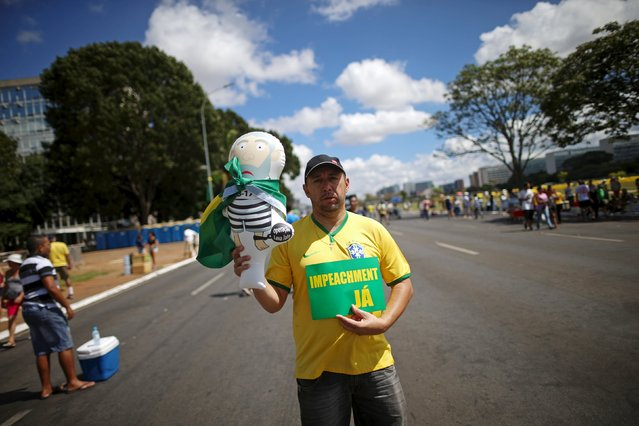 "A man holds an inflatable doll known as ""Pixuleco"" of Brazil's former president Luiz Inacio Lula da Silva, and a sign reading ""Impeachment yes"" in Brasilia, Brazil April 17, 2016. (Photo by Adriano Machado/Reuters)"