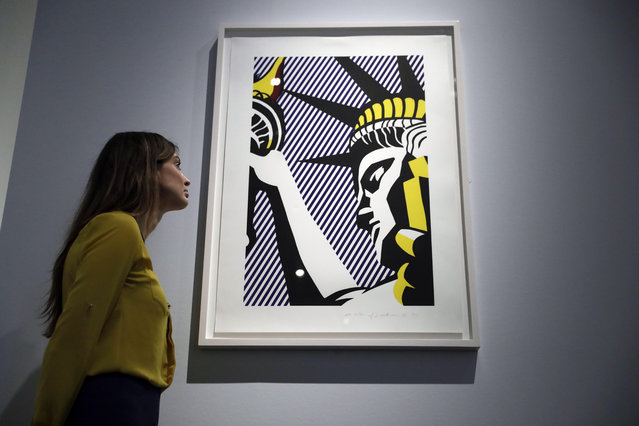 "A British Museum representative poses for photographs next to Roy Lichtenstein's ""I Love Liberty"" which features in ""The American Dream: pop to the present"" exhibition during a media photocall at the British Museum in London, Monday, March 6, 2017. (Photo by Matt Dunham/AP Photo)"