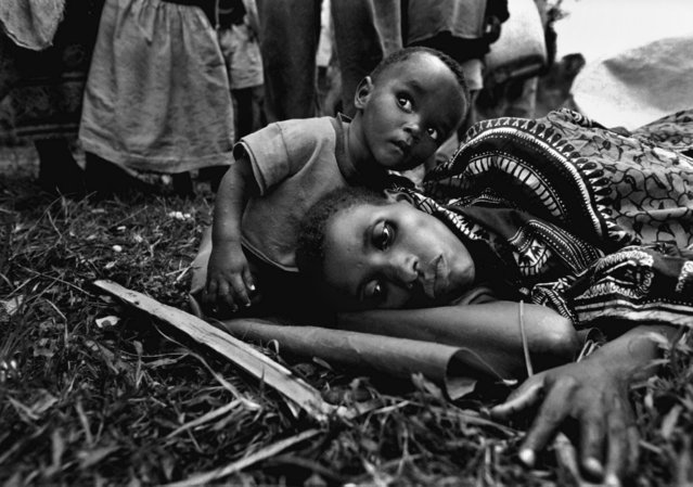 A baby sits next to his mother, who became gravely ill during their journey from Gisenyi, Rwanda, to Kigali, the capital; 1996. (Photo by Carol Guzy/The Washington Post)