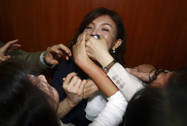 Opposition Democratic Progressive Party (DPP) legislators cover the mouth of Nationalist (KMT) legislator Chao Li-yun during a parliament session inside the Legislative Yuan in Taipei April 21, 2010. (Photo by Reuters/Stringer)