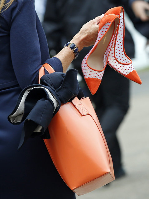 A race goer carrying her shoes arrives for the second day of  Royal Ascot horse racing meet at Ascot, England, Wednesday, June 17, 2015. Royal Ascot is the annual five day horse race meeting that Britain's Queen Elizabeth II attends every day of the event.(AP Photo/Alastair Grant)