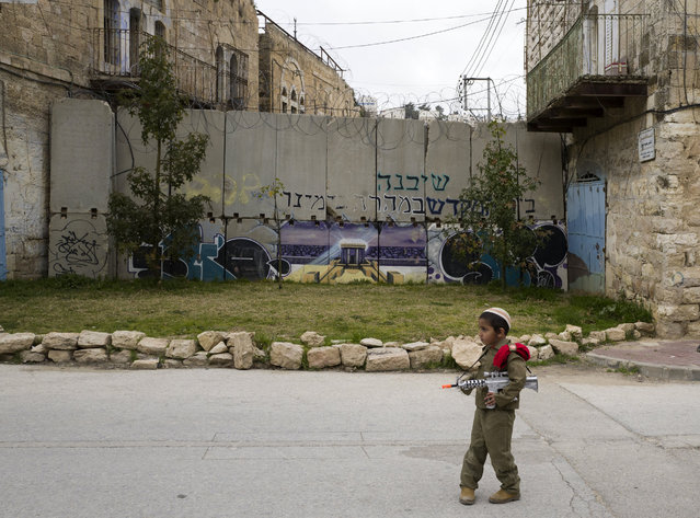 A young Jewish boy dressed in an army costumes stops before a 'separation wall' blocking a street  during the annual Purim parade in the West Bank city of Hebron, 12 March 2017. The joyful Jewish holiday of Purim celebrates the Jews' salvation from genocide in ancient Persia, as recounted in the Scroll of Esther. It is a joyous holiday of drinking in public, dancing and wearing costumes. (Photo by Jim Hollander/EPA)