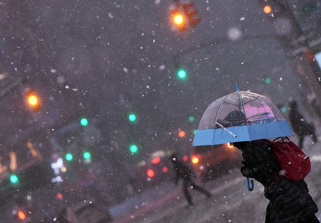 People walk the snow and sleet-covered streets of New York on March 14, 2017. Winter Storm Stella unleashed its fury on much of the northeastern United States on March 14 dropping snow and sleet across the region and leading to school closures and thousands of flight cancellations. Stella, the most powerful winter storm of the season, was forecast to dump up to two feet (60 centimeters) of snow in New York and whip the area with combined with winds of up to 60 miles per hour (95 kilometers per hour), causing treacherous whiteout conditions. But after daybreak the National Weather Service (NWS) revised down its predicted snow accumulation for the city of New York, saying that the storm had moved across the coast. (Photo by Jewel Samad/AFP Photo)