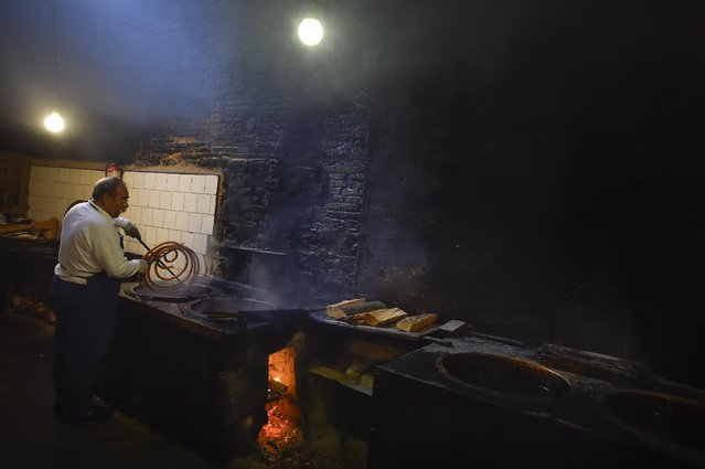 """Elias Elizalde, 66 years old, prepares a """"Churro"""" in the old kitchen of an ancient """"Churreria"""" store, where """"Churros"""", a typical breakfast food, are prepared, in Pamplona northern Spain, Saturday, June 27, 2015.  Since 1871, five generations has taken part in this family tradition. (Зрщещ ин Alvaro Barrientos/AP Photo)"""