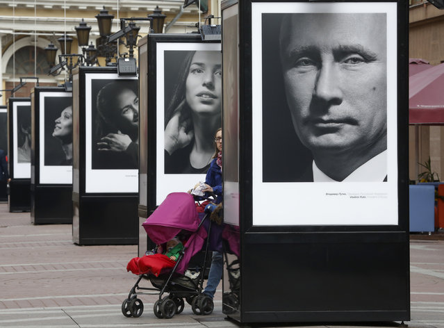 "A woman walks past a portrait of Russian President Vladimir Putin displayed among portraits of Russian athletes, winners of the Sochi 2014 Winter Olympics at the photo exhibition ""Country of the victory. The victory of the country"" in St.Petersburg, Russia, Thursday, May 28, 2015. (Photo by Dmitry Lovetsky/AP Photo)"