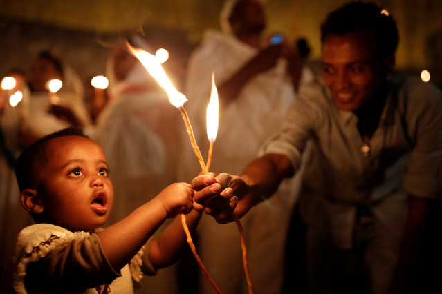 An Ethiopian boy holds candles during the Holy Fire ceremony at the Ethiopian section of the Church of the Holy Sepulchre in Jerusalem's Old City April 30, 2016. (Photo by Amir Cohen/Reuters)