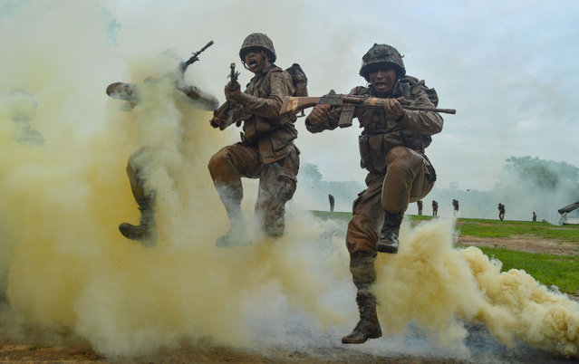 Indian Army recruits shout and jump next to colourful smoke during a training demonstration at the Jak Rifles regimental centre in Jabalpur in Madhya Pradesh state on August 9, 2019. (Photo by Uma Shankar Mishra/AFP Photo)