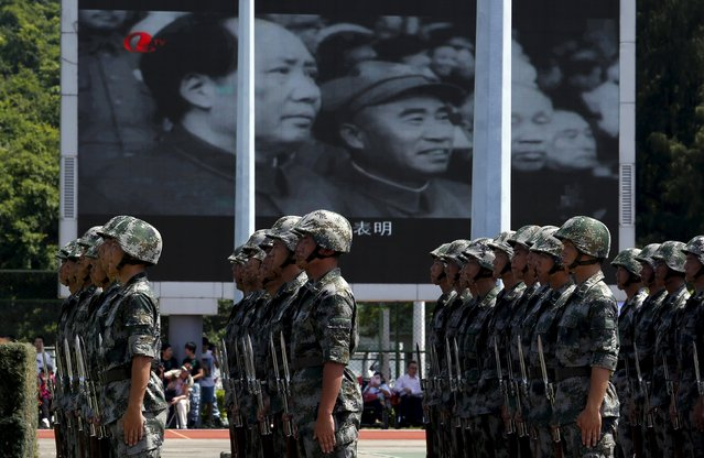 People's Liberation Army (PLA) soldiers stand in front of a panel showing a footage of the late Chinese paramount leader Mao Zedong (L) at a PLA naval base in Hong Kong, China July 1, 2015. (Photo by Bobby Yip/Reuters)