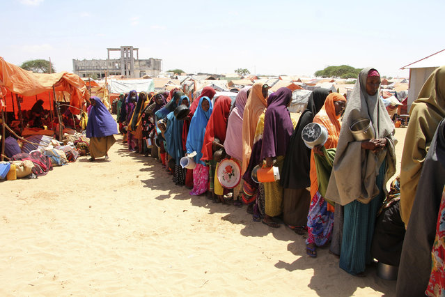 Displaced Somali women stand in a queue to receive food handouts in a camp, just outside of Mogadishu, in Somalia, Monday, March, 27, 2017. Somalia's drought is threatening 3 million lives, according to the U.N. In recent months, aid agencies have been scaling up their efforts but they say said more support is urgently needed to prevent the crisis from worsening. (Photo by Farah Abdi Warsameh/AP Photo)