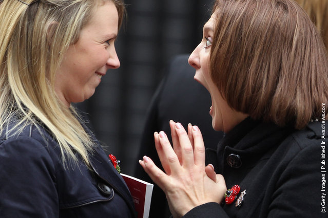Women from the military wives choir joke before singing outside Number 10 Downing Street ahead of a reception with British Prime Minister David Cameron for returning British troops who were involved in operations in Libya