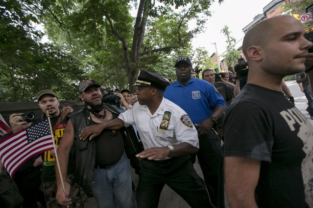 A New York City NYPD officer holds back a crowd from a man (R) who was suspected by the crowd of burning a U.S. flag, following an anti-police protest in Fort Green Park in the Brooklyn Borough of New York July 1, 2015. A crowd against burning the U.S. flag attacked the protesters following the incident, forcing the anti-police protesters to seek aid from members of the NYPD. (Photo by Brendan McDermid/Reuters)