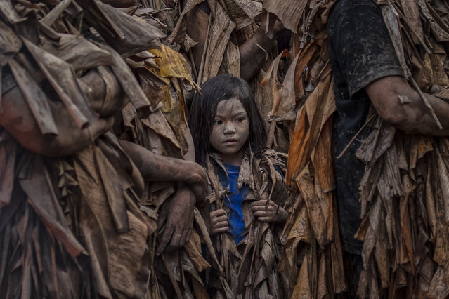 """Devotees covered in mud and dried banana leaves take part in the Taong Putik (""""mud people"""") Festival on June 24, 2019 in the village of Bibiclat in Aliaga town, Nueva Ecija province, Philippines. Each year, the residents of Bibiclat village in Aliaga town celebrate the Feast of Saint John by covering themselves in mud, dried banana leaves, vines, and twigs as part of a little-known Catholic festival. According to locals, the Taong Putik festival (literally meaning """"mud people festival""""), traces its history from the Pacific War and reenacts how rain stopped the execution of 14 villagers by Japanese soldiers in 1944. The townsfolk considered this as a miracle from Saint John, and every year since then the villagers roll in mud to show their gratitude to the saint. The Feast Day of Saint John the Baptist is celebrated throughout the country every June 24. The Philippines is the only Southeast Asian country with a predominantly Catholic majority. (Photo by Ezra Acayan/Getty Images)"""