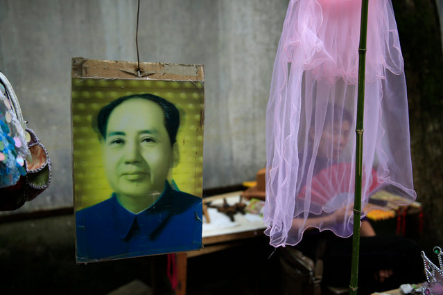 """souvenir hawker fans herself behind a veil at her stall selling Mao Zedong souvenirs outside the """"Water Dripping Cave"""" compound, where Mao Zedong stayed briefly for 11 days in 1966 and is thought to have contemplated the start of the Cultural Revolution there in Shaoshan, Hunan Province in central China, 28 April 2016. (Photo by How Hwee Young/EPA)"""