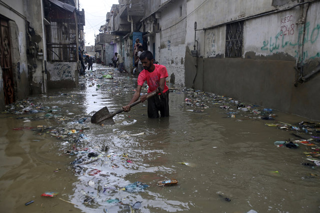 A man cleans a flooded street after a heavy rainfall, in Karachi, Pakistan, Tuesday, July 30, 2019. The Pakistan Meteorological Department said that a rain system entered Sindh province from India's Rajasthan and forecasts another three days of rain. (Photo by Fareed Khan/AP Photo)