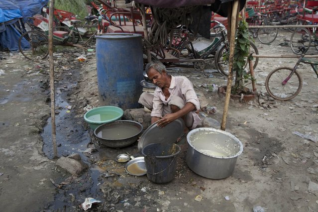 """An Indian man washes utensils of a roadside food vendor in New Delhi, India, Tuesday, June 30, 2015. The millions of food vendors peddling tasty morsels from roadside stalls and rickshaws across India have no training on the basics of food safety and hygiene, and many an adventurous snacker have been struck down by the infamous """"Delhi belly"""". (Photo by Tsering Topgyal/AP Photo)"""