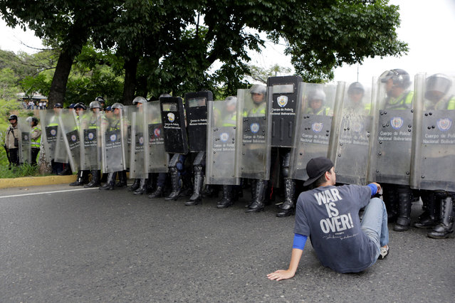 An opposition supporter sits in front of riot policemen in a rally to demand a referendum to remove President Nicolas Maduro in Caracas, Venezuela, May 11, 2016. (Photo by Marco Bello/Reuters)