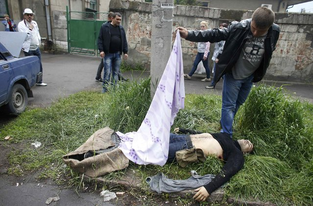A man looks at a dead body after Ukrainian forces attacked police headquarters in an attempt to drive out pro-Russian militants in Mariupol May 9, 2014. Ukrainian security forces killed about 20 pro-Russian rebels who tried to seize control of police headquarters in the eastern port city of Mariupol on Friday, the Interior Minister said. (Photo by Marko Djurica/Reuters)
