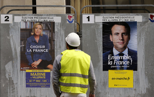 A worker looks at electoral posters of French presidential election candidate for the En Marche ! (Onwards!) movement Emmanuel Macron (R) and French presidential election candidate for the far-right Front National (FN) party Marine Le Pen (L) on April 28, 2017 in Paris, France. Le Pen and Macron arrived in the lead positions in the first round of the presidential elections. France will hold the second round on May 07, 2017. (Photo by Chesnot/Getty Images)