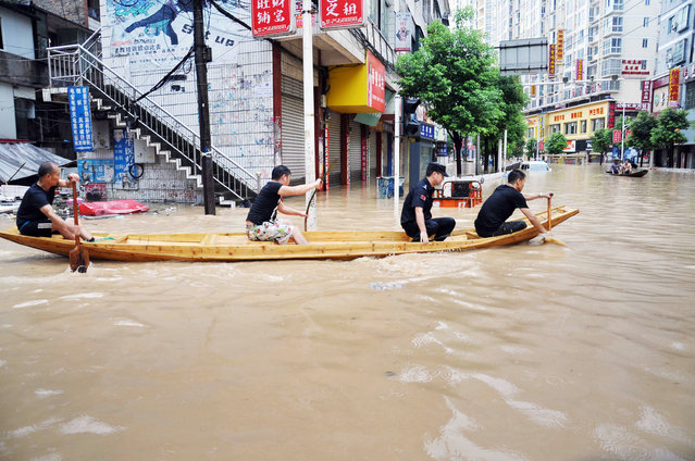 Rescuers row a wooden boat through a flooded neighborhood in Songtao county in southwestern China's Guizhou province Wednesday, July 15, 2015. Torrential rains hit parts of southwestern China late Tuesday and caused flooding. (Photo by Chinatopix Via AP Photo)
