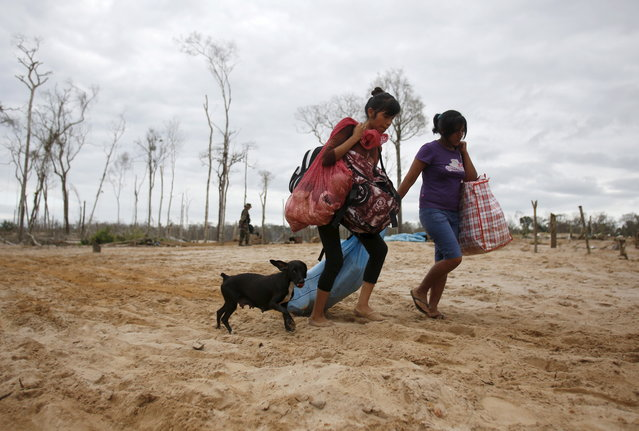 People leave a camp after a Peruvian police operation to destroy illegal gold mining camps in a zone known as Mega 14, in the southern Amazon region of Madre de Dios July 14, 2015. (Photo by Janine Costa/Reuters)