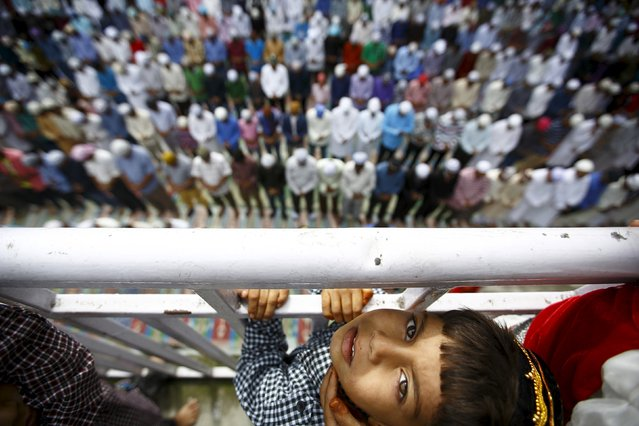 A Muslim boy stands next to the fence as Nepali Muslims attend a mass prayer during Eid al-Fitr celebrations at a mosque in Kathmandu July 18, 2015. (Photo by Navesh Chitrakar/Reuters)