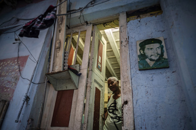 """In this November 10, 2019 photo, Lorenzo Ballester poses at the door of his house, decorated with a photo of revolutionary hero Ernesto """"Che"""" Guevara, in Havana, Cuba. (Photo by Ramon Espinosa/AP Photo)"""