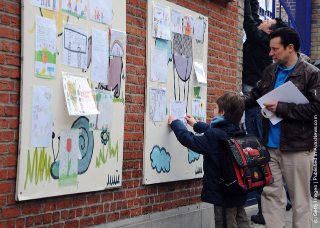 A school child puts up a picture at the gates of Sint Lambertus School, following a bus crash that killed 22 children in Switzerland, on March 14, 2012 in Heverlee, Belgium