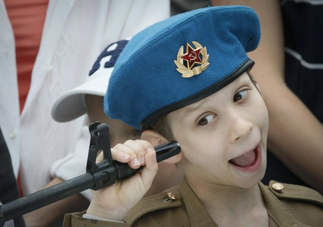 A boy plays with a machine gun at a weapon exhibition, during celebrations for Navy Day in St.Petersburg, Russia, Sunday, July 26, 2015. (Photo by Dmitry Lovetsky/AP Photo)