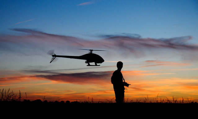 16 year-old Yanik Wolter controls a model helicopter during sunset on a field in Gleidingen near Hannover, northern Germany, Thursday, June 12, 2014. The small helicopter with up to 1.50 meters wingspan is remotely controlled. With top speeds of over 200 kilometers per hour, the model flyer steers the helicopter over secure meadows and cornfields. (Photo by Julian Stratenschulte/AP Photo/DPA)