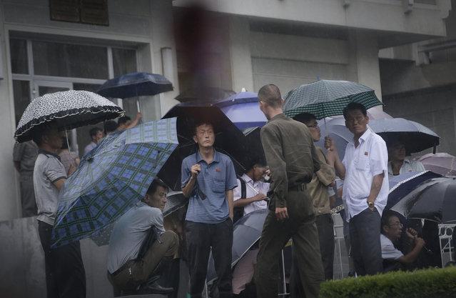 North Koreans wait outside a popular noodle restaurant, Saturday, July 25, 2015, in Pyongyang, North Korea. (Photo by Wong Maye-E/AP Photo)