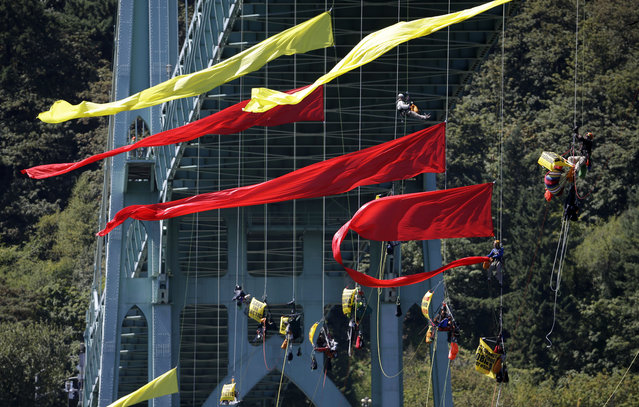 Activists unfurl colored banners while hanging from the St. Johns bridge in Portland, Ore., Wednesday, July 29, 2015, to protest the departure of Royal Dutch Shell PLC icebreaker Fennica, which is in Portland for repairs. (Photo by Don Ryan/AP Photo)