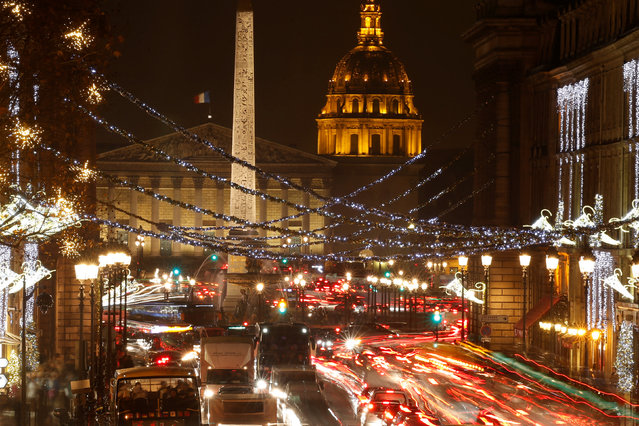 Christmas holiday lights hang from trees to illuminate the rue Royale in front of the Place de la Concorde, the Luxor Obelisk and the Dome des Invalides as part of illuminations for the Christmas holiday season in Paris,  France, December 22, 2016. (Photo by Charles Platiau/Reuters)