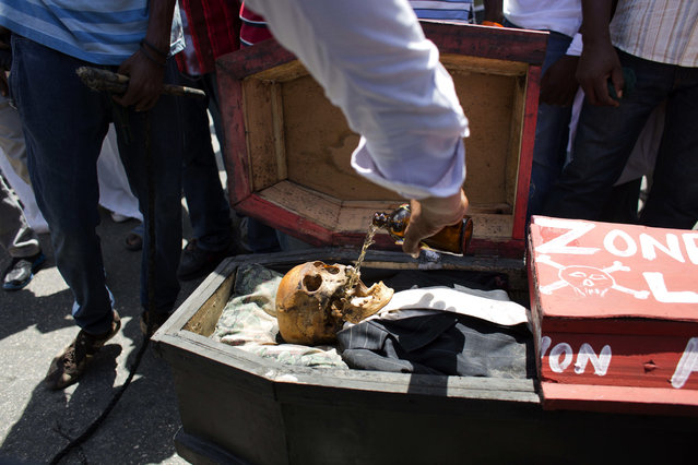 A supporter of the PHTK presidential candidate Jovenel Moise pours beer into the skeleton skull meant to represent interim President Jocelerme Privert in a mock coffin, during a voodoo ceremony, before the start of a protest march demanding his resignation in Port-au-Prince, Haiti, Tuesday, June 7, 2016. The electoral council of Haiti has decided to re-do a presidential election that a special commission determined was marred by fraud. (Photo by Dieu Nalio Chery/AP Photo)