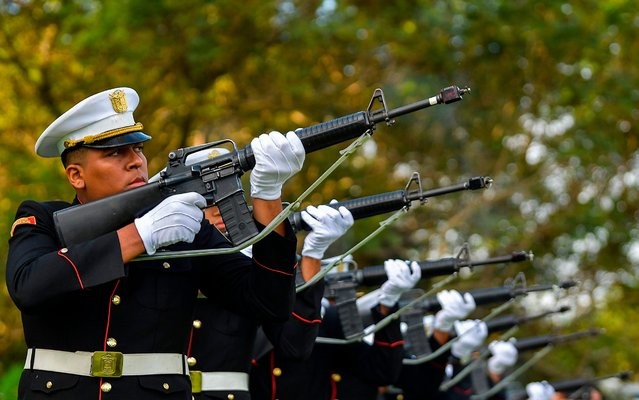 Members of Panama's presidential guard fires into the air during a solemn ceremony commemorating the 30th anniversary of US military invasion at the Jardin de la Paz cemetery in Panama City, on December 20, 2019. Al least five hundred people died and over 2,000 were injured during the invasion aimed to oust Panama's General Manuel Antonio Noriega from power and take him to the US to be tried on drug charges. (Photo by Luis Acosta/AFP Photo)