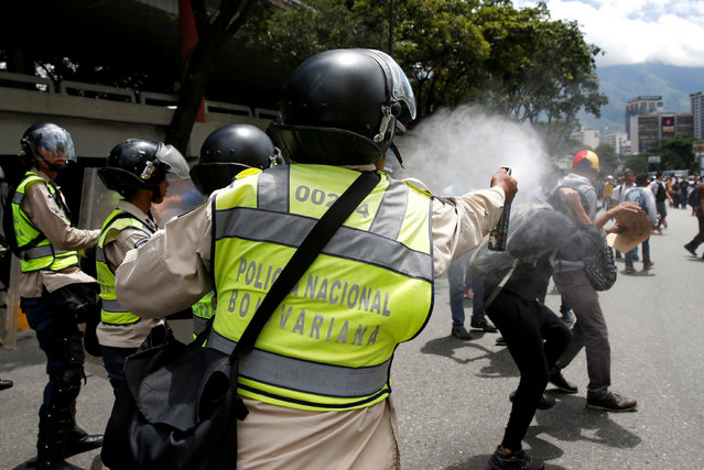 A police officer uses tear gas on demonstrators during a protest called by university students against Venezuela's government in Caracas, Venezuela, June 9, 2016. (Photo by Carlos Garcia Rawlins/Reuters)